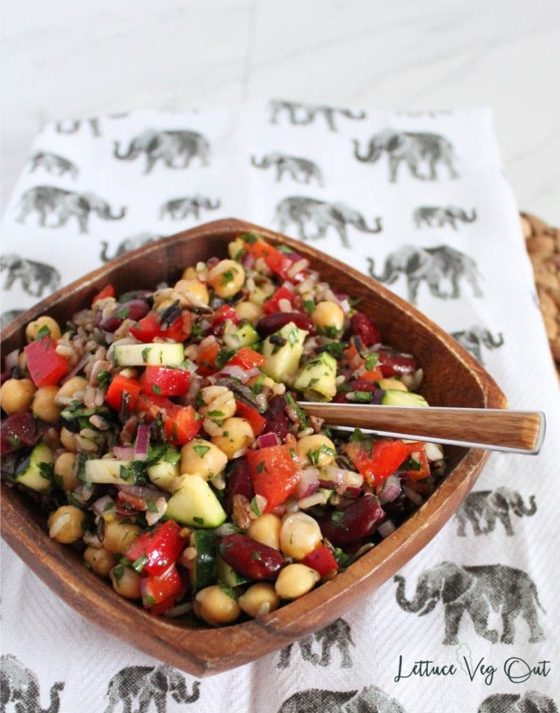 Square wooden bowl filled with mixed bean and wild rice salad with wooden spoon in bowl and bowl on top of elephant patterned towel