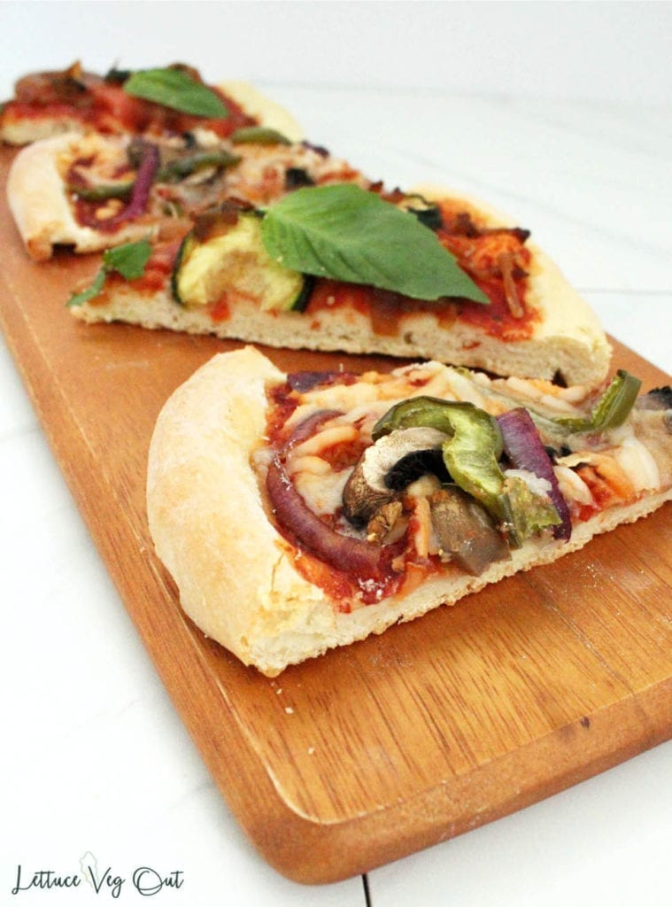 Classic vegan pizza toppings on homemade vegan pizza dough (slices on wooden board)