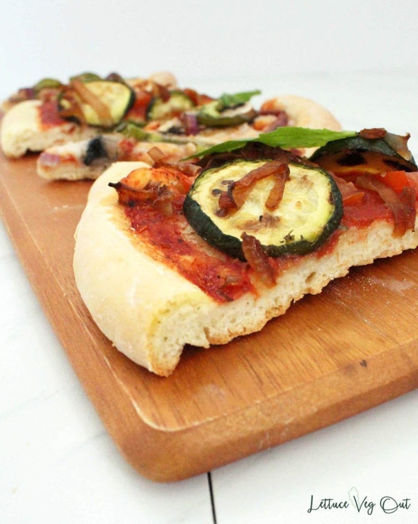 Gourmet pizza toppings on vegan cornmeal pizza crust (slices on wooden board)