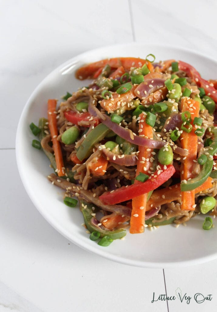 White plate filled with soba noodle stir fry with peanut sauce and colorful vegetables (carrots, red bell pepper, edamame) and topped with sprinkle of white sesame seeds