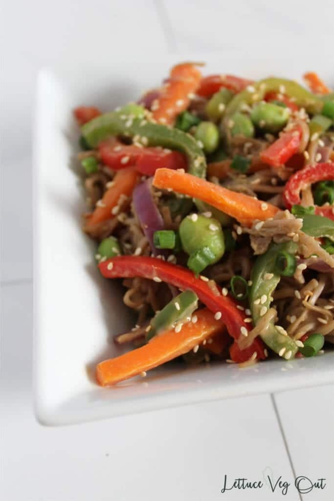 Close up of square white bowl filled with buckwheat noodle stir fry with vegetables and peanut sauce, topped with a sprinkle of white sesame seeds
