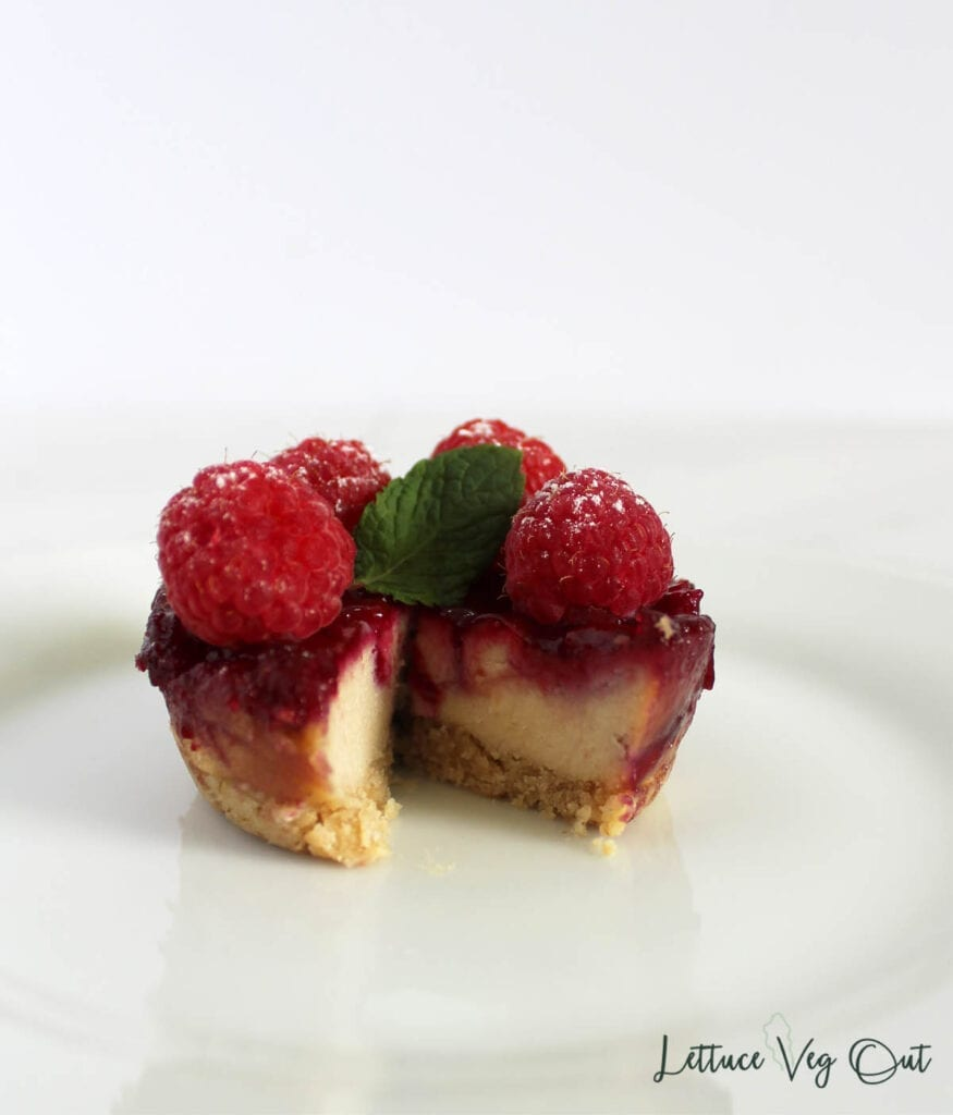Vegan raspberry cheesecake with piece cut out, topped with fresh raspberries and mint leaf