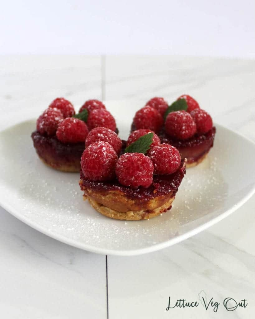 Three vegan cheesecake bites on a plate topped with raspberries