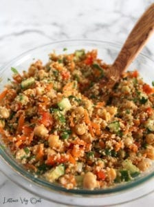 Vegan Mediterranean salad with couscous, chickpeas, cucumber, carrot, red pepper and a lemon vinaigrette in a glass bowl with large wooden spoon