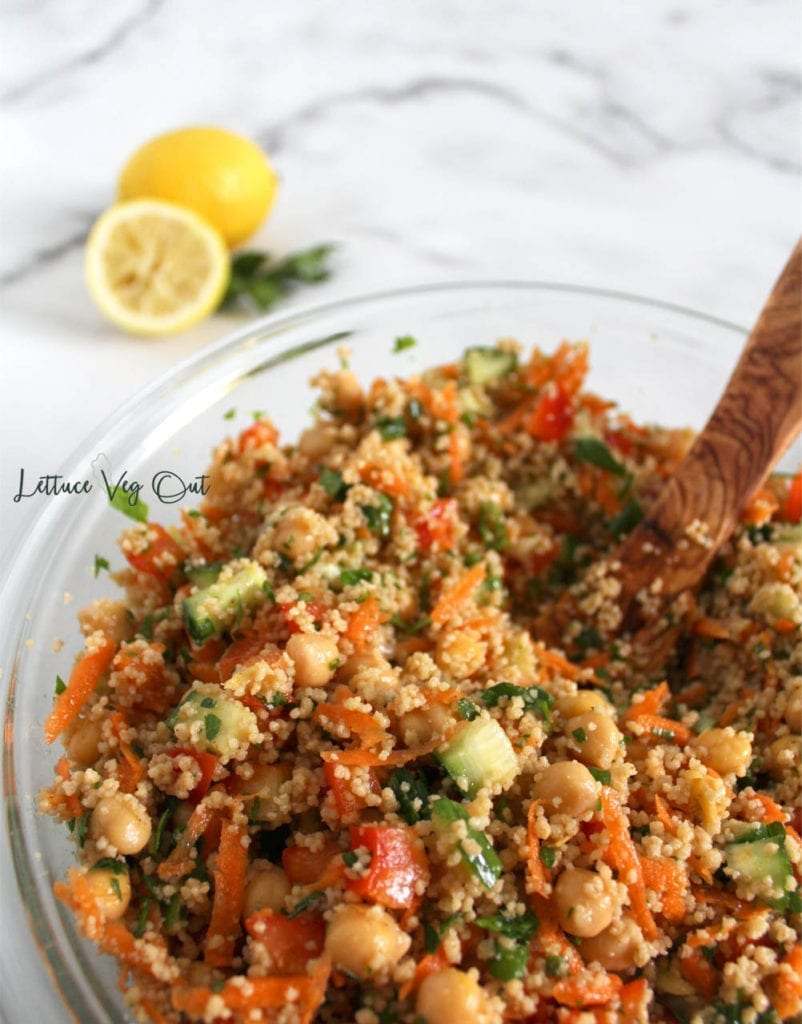 Vegan Mediterranean chickpea salad with Moroccan couscous in large glass bowl with wooden spoon and parsley with lemon in background