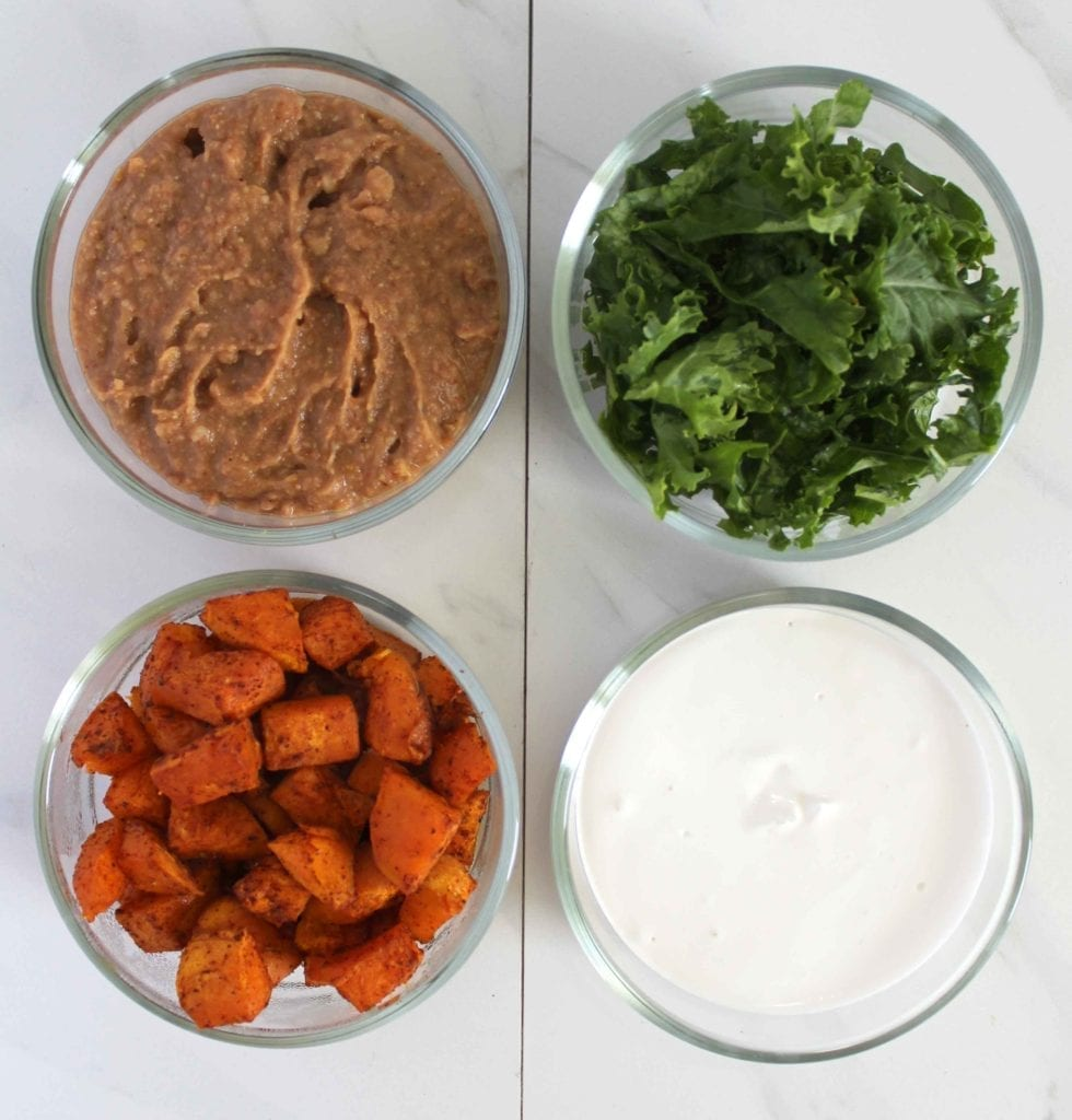 Vegan roasted sweet potatoes tossed in taco seasoning with refried beans and kale