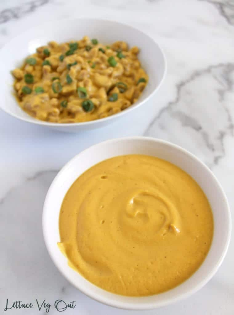 White bowl of vegan sweet potato cheese sauce with pasta bowl in background