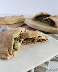 Cut open vegan calzone with classic filling and pesto calzone in background