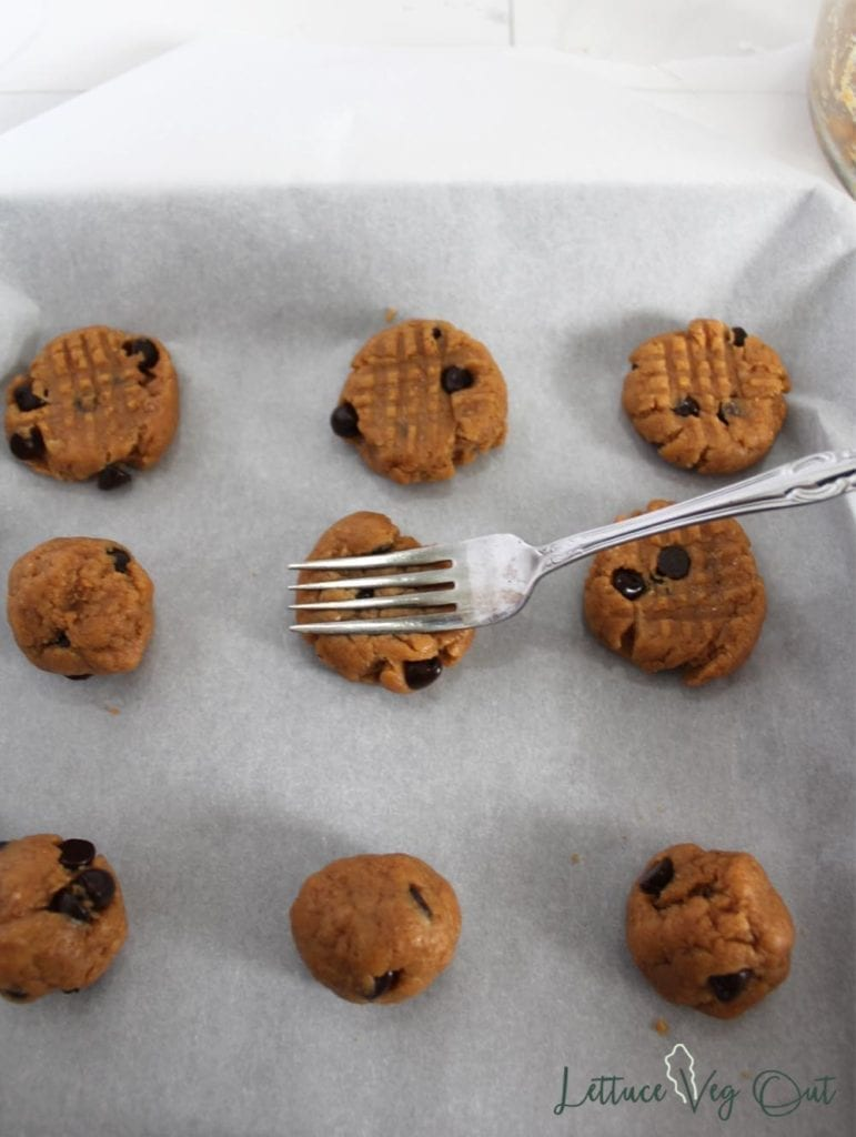 Fork flattening peanut butter chocolate chip cookies on a baking tray