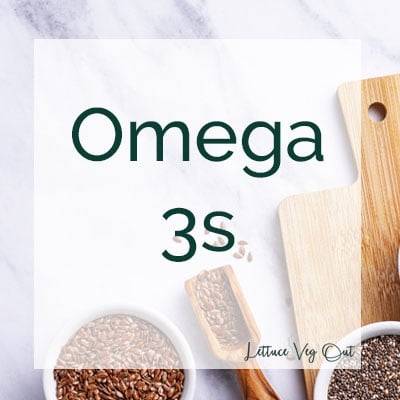Omega 3s text over background of marble and flaxseeds/ chia seeds in ceramic jars on wooden cutting board