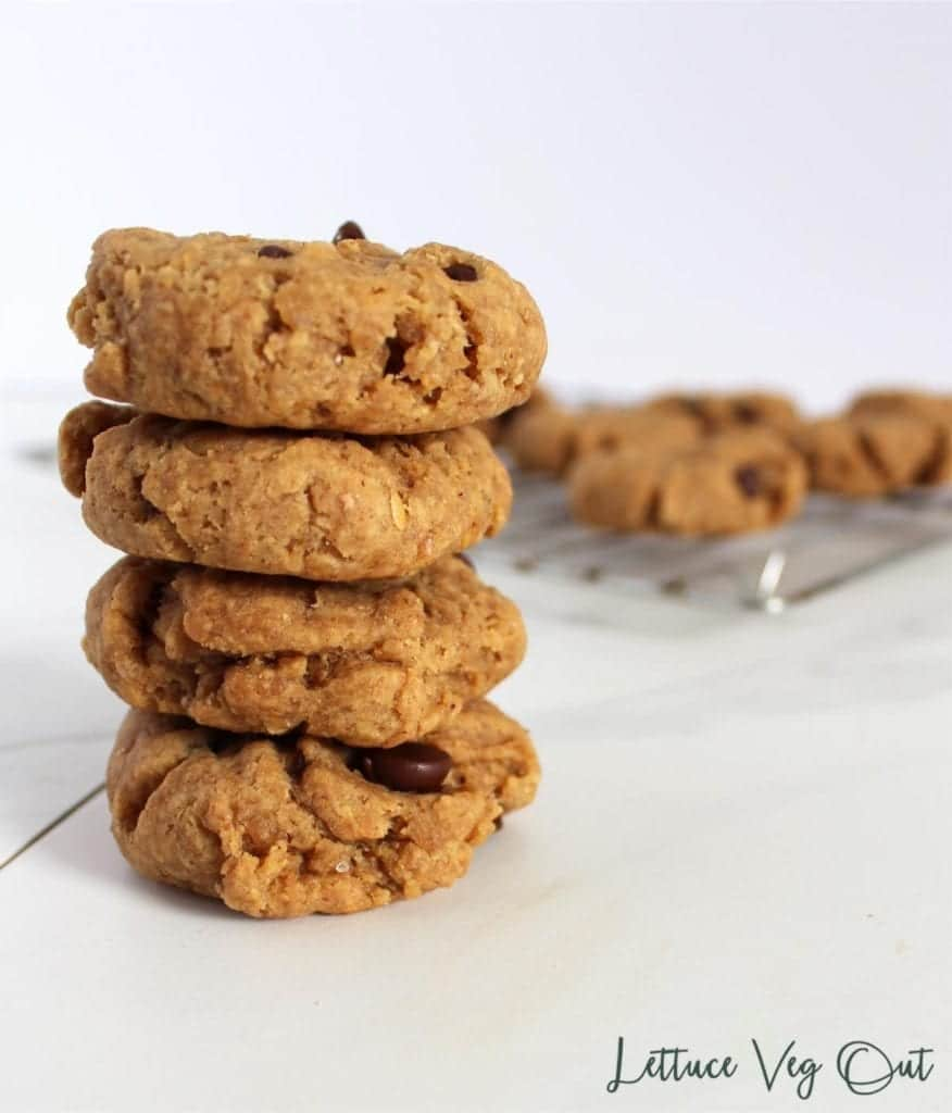 Stack of vegan peanut butter cookies in front of a cooling rack with more cookies on it