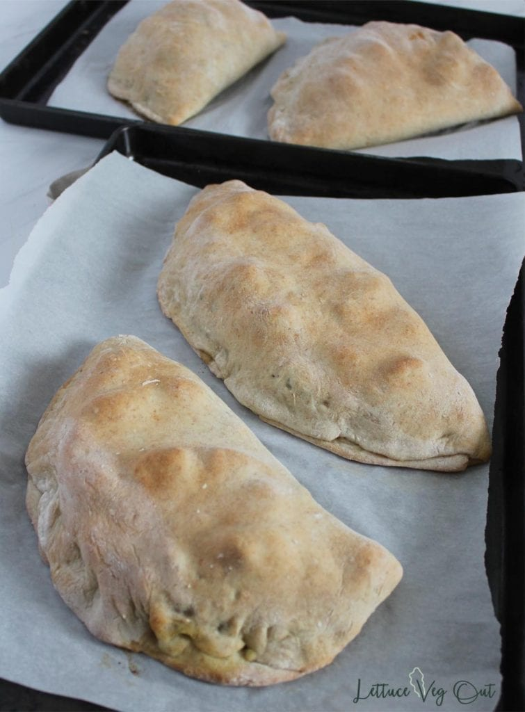 Baked calzones on baking trays