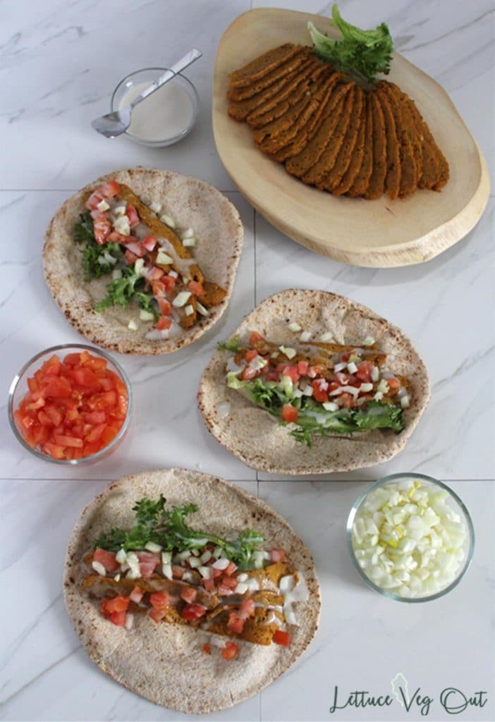 Flat layout of Halifax donair ingredients including tomato, onion, sweet sauce and vegan donair meat sliced on a wooden cutting board; 3 assembled wraps laid out unwrapped