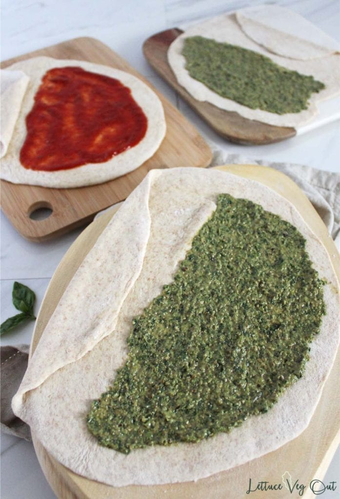 Vegan pesto on dough showing how to make homemade calzone (second calzone covered in red pizza sauce in the background)