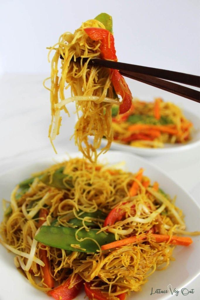 Bite of gluten free vegan noodles held in chopsticks above plate