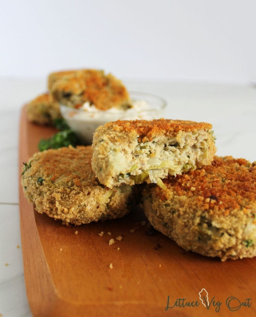 Vegan artichoke crab cakes on a wooden serving platter with sour cream dip