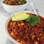 Two white bowls of vegan chili topped with avocado