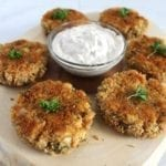 Vegan hearts of palm crab cakes with dipping sauce on a wooden cutting board