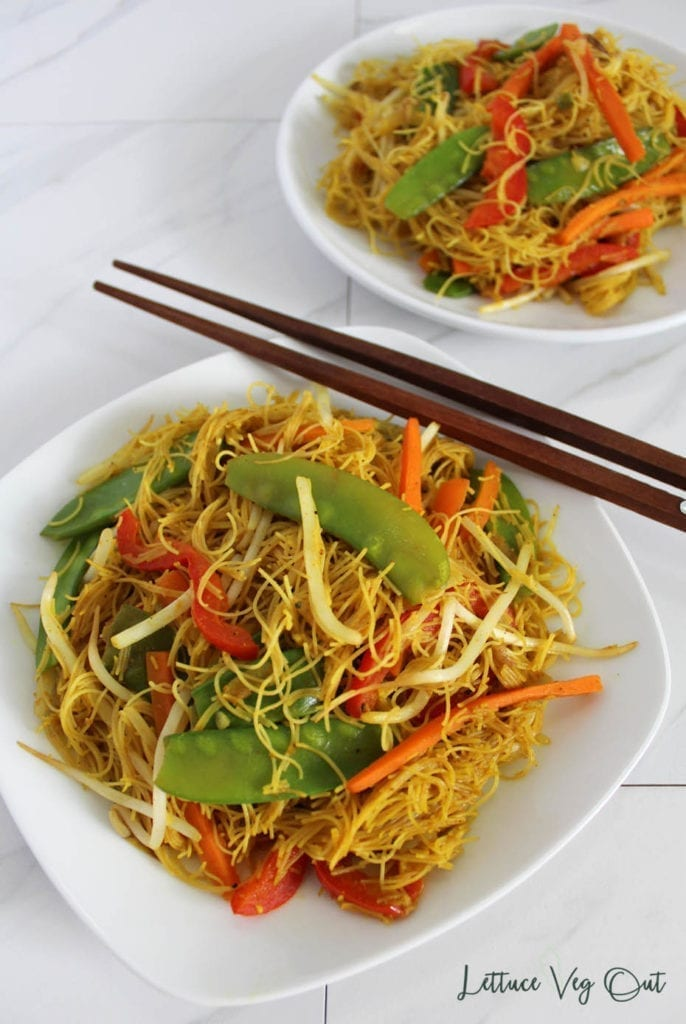 Close-up image of curry vermicelli noodles with mixed vegetables on a white plate