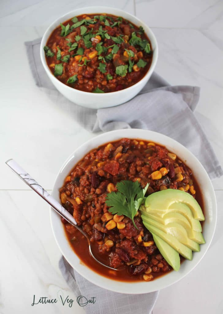 Two bowls of vegan chili topped with cilantro and avocado on a marble background