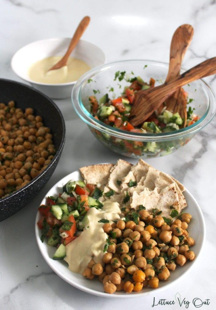 Vegan falafel plate dinner with hummus sauce and cucumber tomato salad