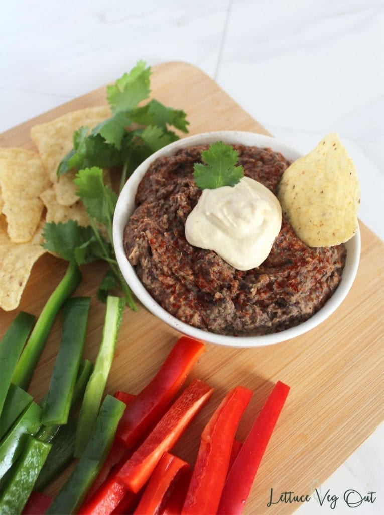 Vegan and gluten free black bean dip topped with a scoop of vegan sour cream