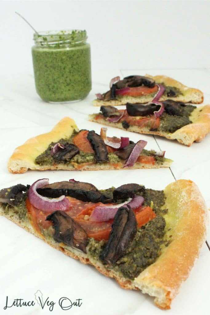 Slices of vegan pizza with pesto sauce and balsamic mushrooms