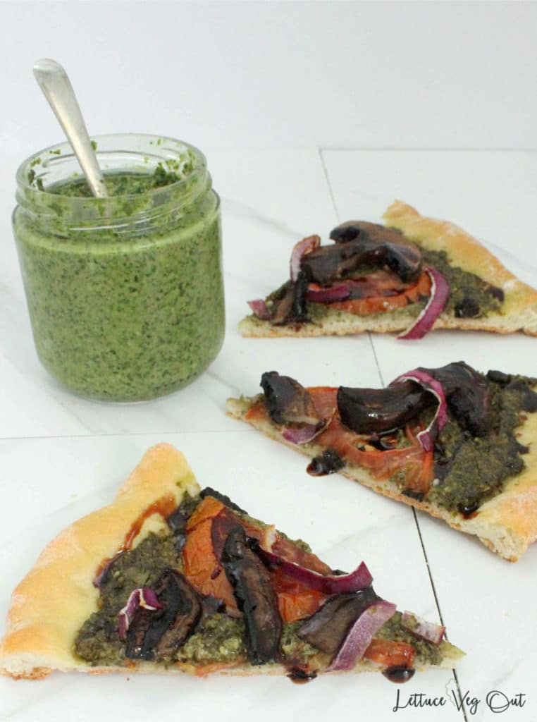 Slices of vegan pizza with a jar of pesto