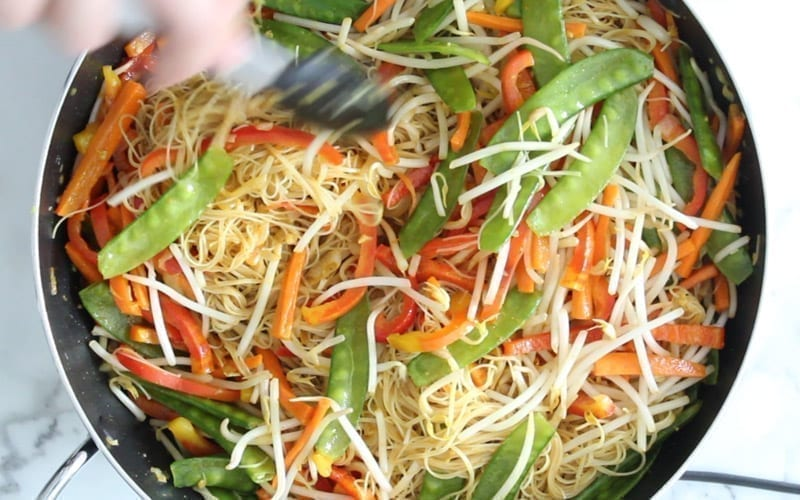 Stir fry Singapore noodle vegetables, noodles and sauce together in a pan over heat