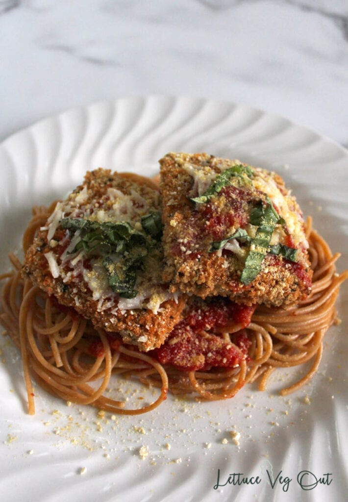 Two pieces of vegan chicken parmesan on top of pasta with tomato sauce and Parmesan cheese