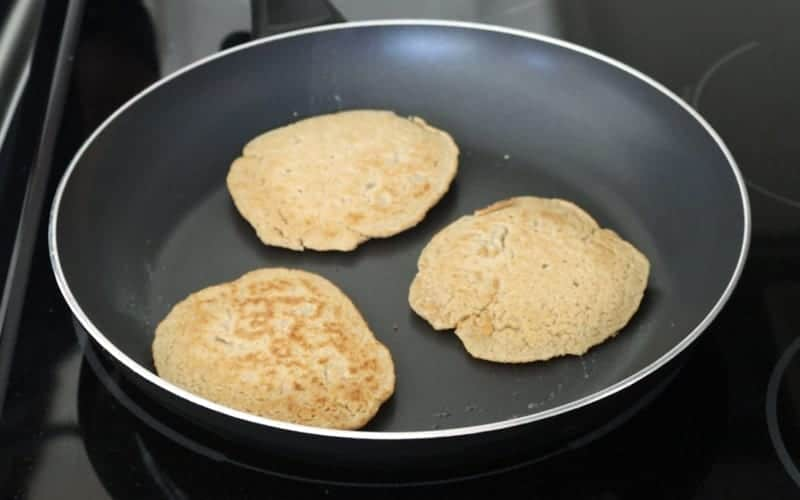 Vegan oatmeal pancakes that have been flipped and show a golden-brown color in the frying pan. Almost ready to serve.