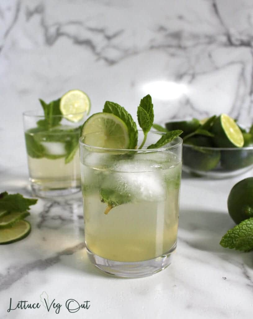 Two short glasses of lime mint mocktails with bowl of limes in back