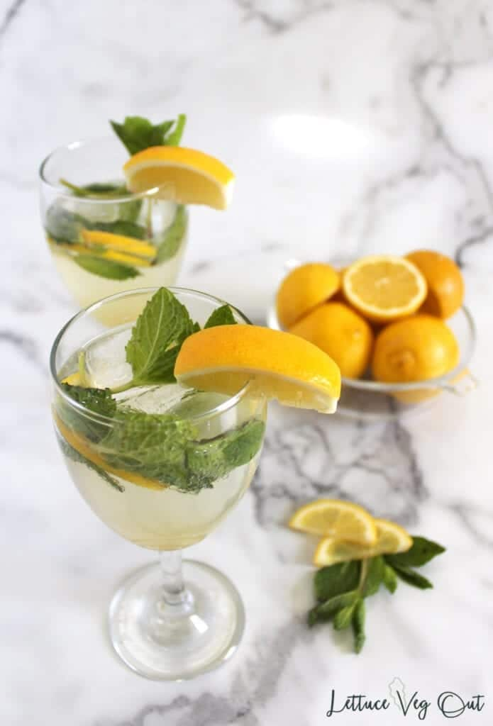 Top view of two wine glasses with lemon mojito mocktail with mint leaf and lemon wedge garnish