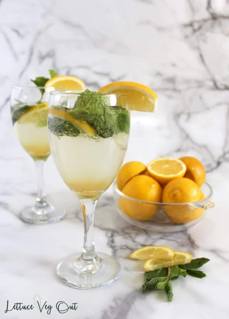 Two un-stirred wine glasses filled with mint lemon mocktail with bowl of lemons to the back right (marble background)