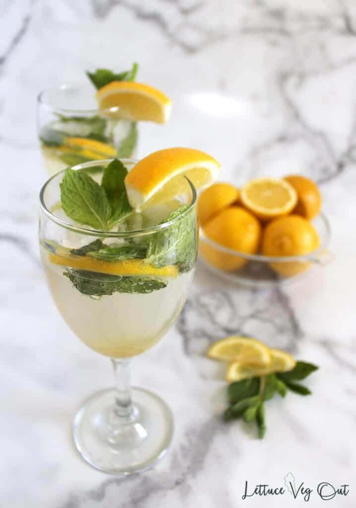 Two wine glasses filled with lemon mocktail, garnishes with lemon slices and mint leaves (marble backdrop)