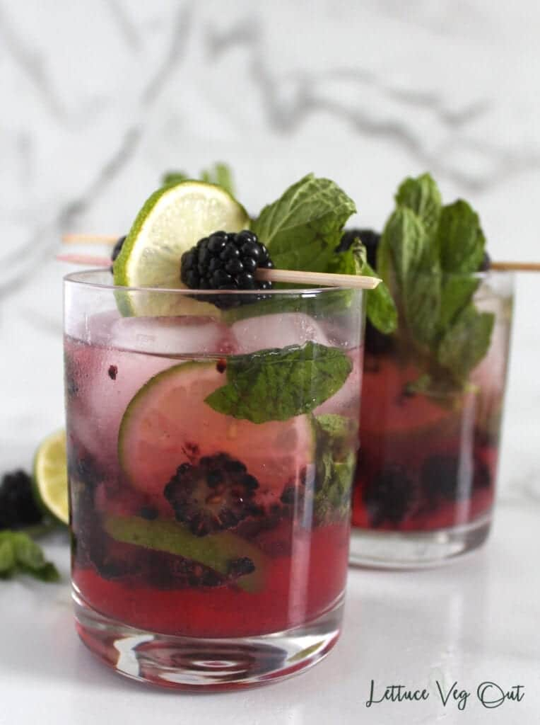 Two glasses of blackberry mojito mocktails garnished with mint leaves, lime slices and fresh blackberries