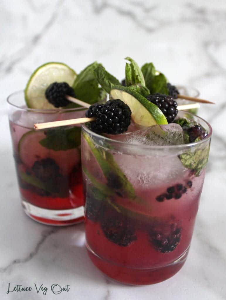 Three glasses of purple blackberry mocktails garnished with blackberry, mint and lime skewers