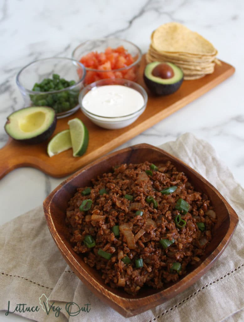 Wooden bowl of TVP taco meat with vegan taco filling options on wooden board in back (avocado, lime, green onion, tomato, corn tortilla)