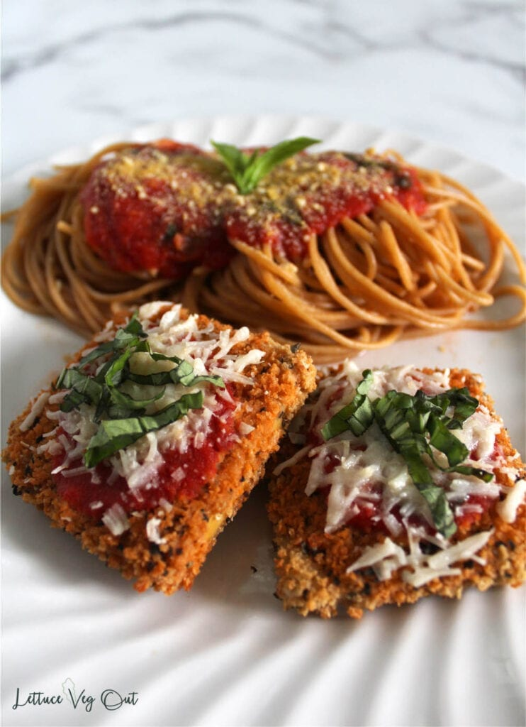 Two pieces of vegan chicken parm on white plate with pile of spaghetti pasta topped with sauce and parmesan cheese