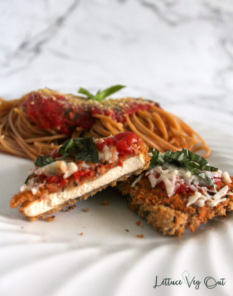 Cut open piece of breaded and baked tofu on plate with pasta and tomato sauce