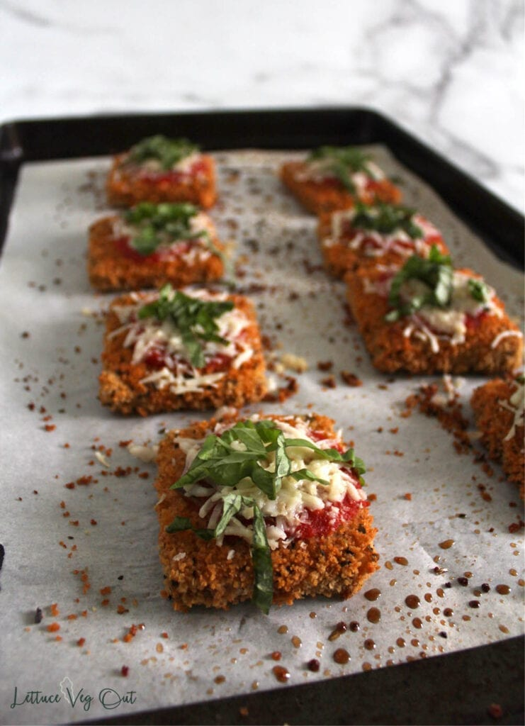 Baking tray of baked vegan tofu parmesan pieces topped with tomato sauce, cheese and fresh basil