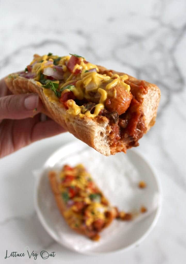 Vegan chili dog in whole wheat bun being held up above plate with another hot dog on it