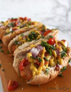 Row of vegan chili cheese dogs topped with red onion, tomato and cilantro on a wooden board