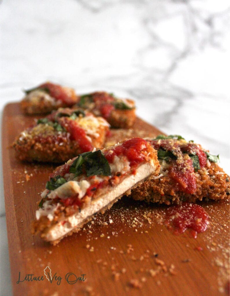 Wooden board of vegan tofu parmesan pieces with one cut open to show texture of the tofu