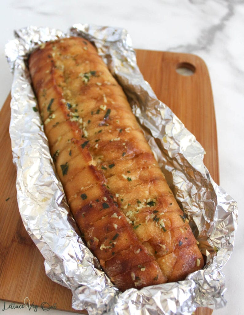 Loaf of baked garlic bread, sliced across the top, in tin foil wrap on wooden board