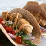 Close up of vegan fish tacos with beer battered tempeh in tortilla with Baja sauce, tomato, red onion and slaw