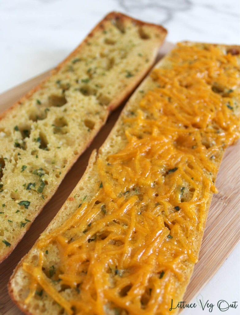 """Two halves of dairy free garlic bread load, one half with melted dairy free cheddar """"cheese"""" shreds melted on top"""