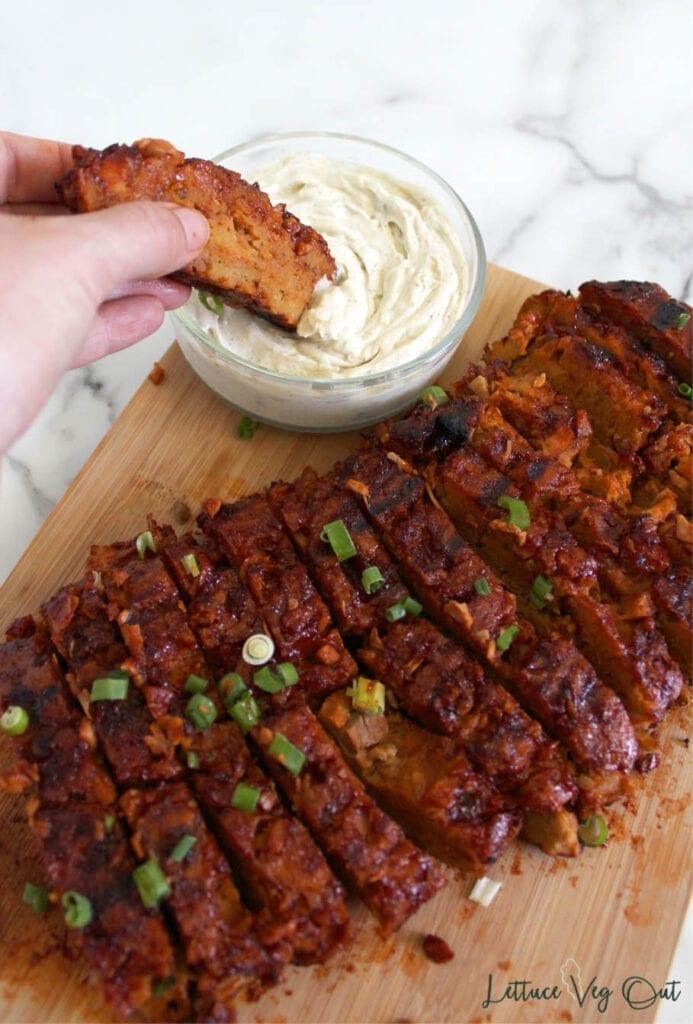 Hand dipping a slice of BBQ seitan into creamy dip
