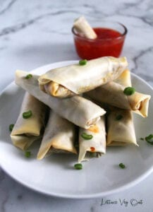 Stack of baked vegetable spring rolls on a plate with green onion sprinkle and glass dish of chili sauce in back with a spring roll dipped in it