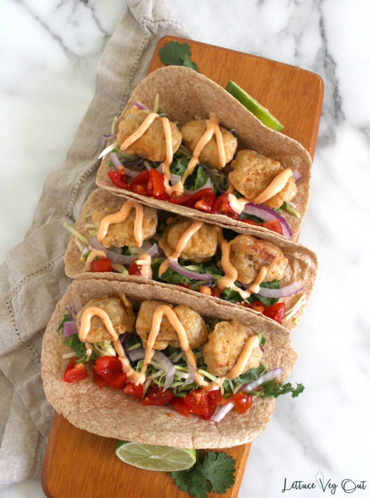 Top view of 3 vegan fish tacos on wooden board